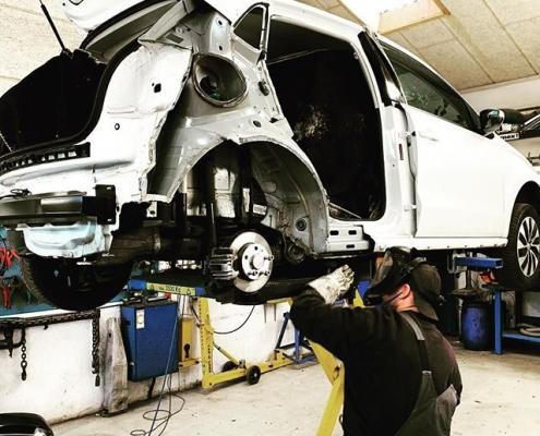 automekaniker udbedrer autoskade på værskted